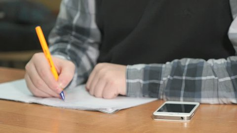 Unknown man in grey shirt with black pullover sitting at desk at lesson at university writes text using ball pen in notebook. Student looks at silver mobile phone for important information