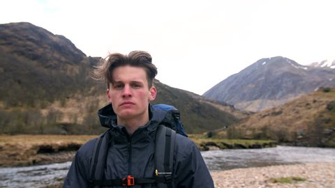 4K Portrait of handsome traveller standing in front of Ben Nevis mountain in Scottish Highland. Hiker and backpacker in front of river in front of Scotland UK