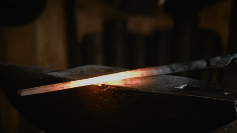 Blacksmith manually forging the molten metal on the anvil in smithy with spark
