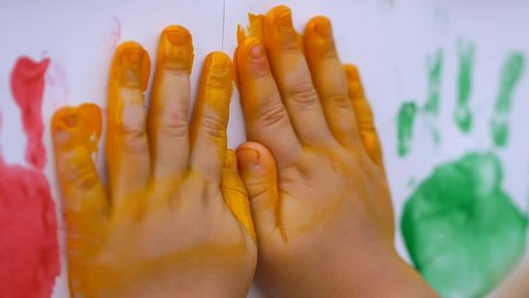 Close up of little child's hands making color handprints in the white wall in slow motion 50fps