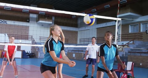 Female volleyball players playing volleyball in the court 4k