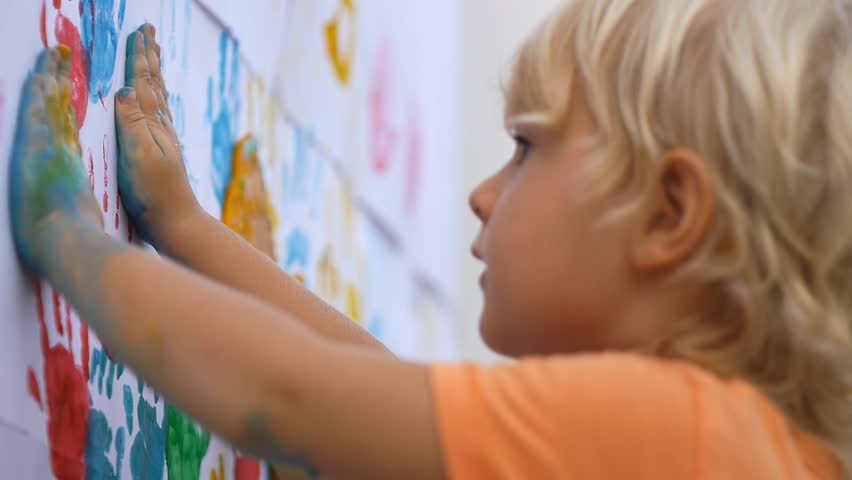 Close up of happy little child making colorful handsprint on the white wall with mother together. Slow motion 50fps | Shutterstock HD Video #10112810