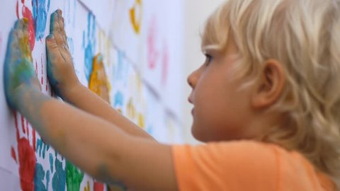 Close up of happy little child making colorful handsprint on the white wall with mother together. Slow motion 50fps