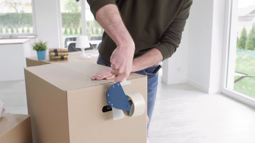 Man with adhesive tape packing boxes