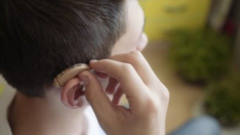 the young man wears a hearing aid. Man with hearing aid