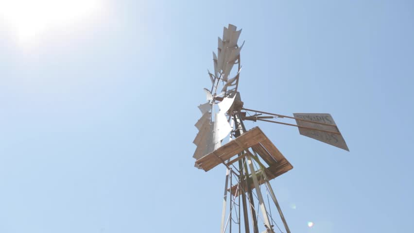 Windmill windpump pumping water in the dry arid region of the Tankwa Karoo of South Africa with the bright sun shining on it.