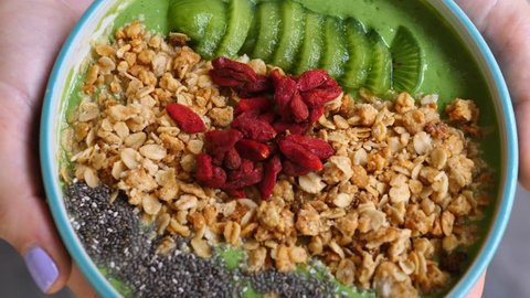 Closeup Of Vegan Avocado Green Smoothie Bowl Topped With Granola, Chia And Goji