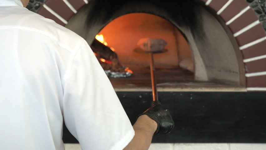Unrecognizable Male Baker takes out of the Bread into Wood Burning Stove for Baking. Chef Bakes Flatbread Pita in a Stone Oven