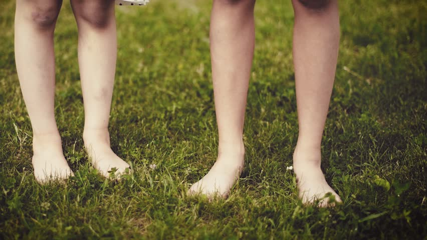 Slow motion shot of bare feet of little girls walking, jumping and running on green grass. Happy children playing outdoors in spring or summer park. Fun at field - retro.  #1011337640