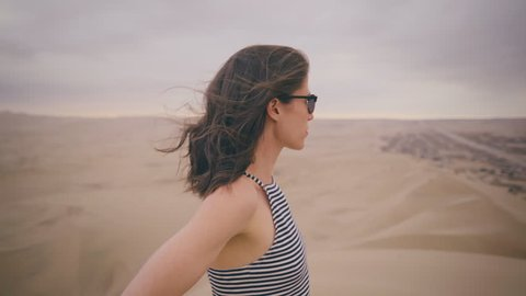 Portrait of Young Woman taking in landscape with hair blowing in wind looking at sunset at a desert oasis wearing white/black stripped fashionable tank shirt in Peru