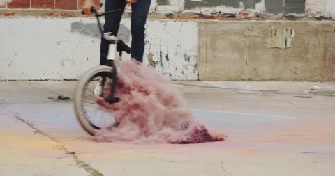 Close up of extreme BMX biker riding through pile of colored powder in slow motion