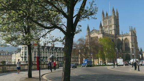 Bath Abbey, UK. Sunshine day, wide angle, trees in foreground. Blue sky. Roads. First king of England crowned here.