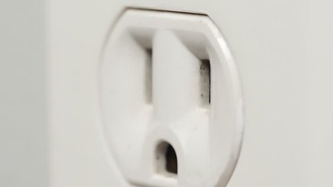 Extreme closeup of an appliances plug being inserted into an electric outlet.