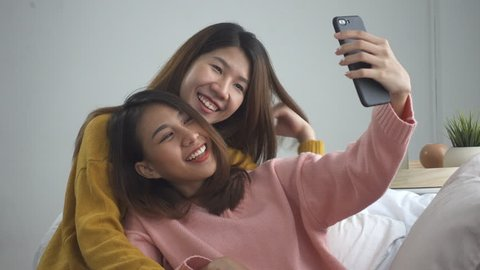 Beautiful young asian women LGBT lesbian happy couple sitting on sofa hug and using phone taking selfie together bedroom at home. LGBT lesbian couple together indoors concept. Spending nice time home.
