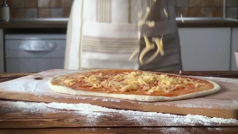 A female hand sprinkles a pizza with grated cheese close-up. super slow motion