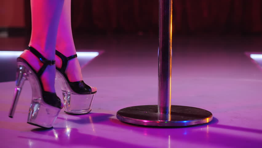 Young sexy slim woman pole dancing striptease with pylon in night club. Beautiful stripper girl on stage. Slow motion.   Shutterstock HD Video #1011437840
