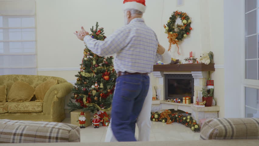 Old couple are dancing at home near christmas tree | Shutterstock HD Video #1011438770