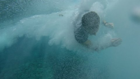 SLOW MOTION, LOW ANGLE, UNDERWATER: Beginner surfer crashes into crystal clear water while he tries to stand up on surfboard. Funny shot of man falling into the turquoise water while trying to surf.