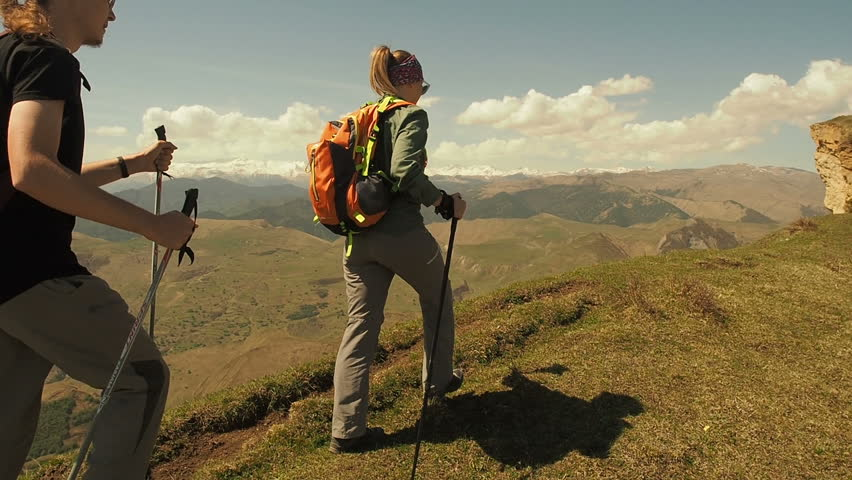 Hikers People Hiking Walking With Trekking Poles. Young active man and woman climbing mountain, couple spending summer vacation together. Happy people travelers  travel enjoy view. Hike in mountains.  | Shutterstock HD Video #1011456050