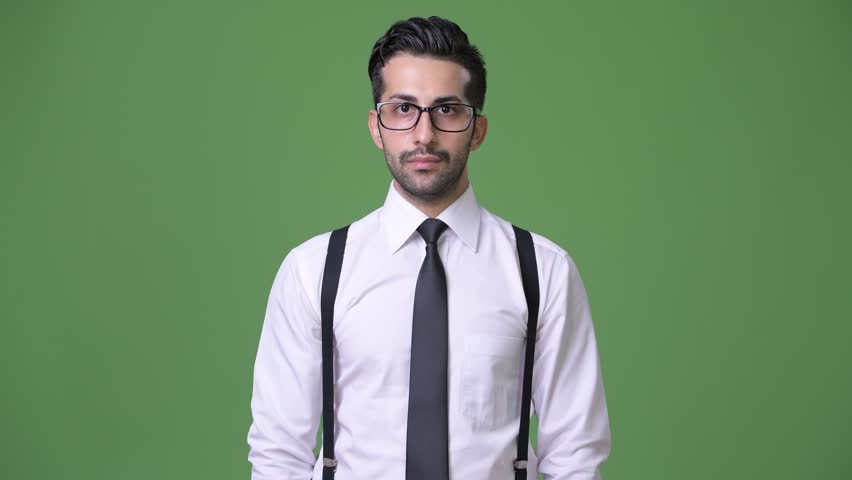 Young handsome bearded Persian businessman against green background | Shutterstock HD Video #1011456980