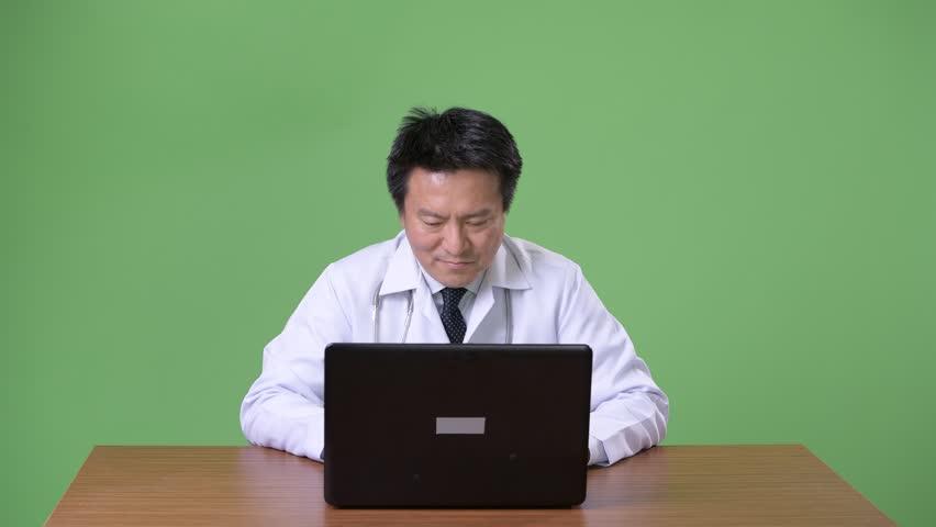 Mature Japanese man doctor against green background | Shutterstock HD Video #1011457130