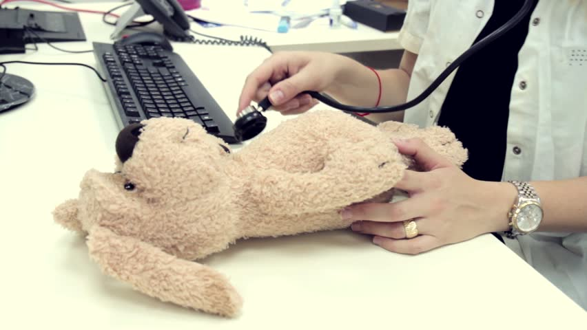 Stuffed Dog animal presented as a pediatrician holding a stethoscope.    Shutterstock HD Video #1011476360
