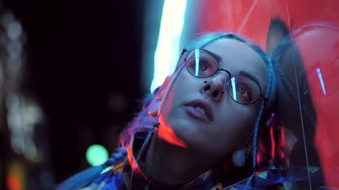 Millennial sad pretty girl with unusual hairstyle near glowing neon of the city at night. Dyed blue hair in braids. Mysterious hipster teenager in glasses. Reflection of light.