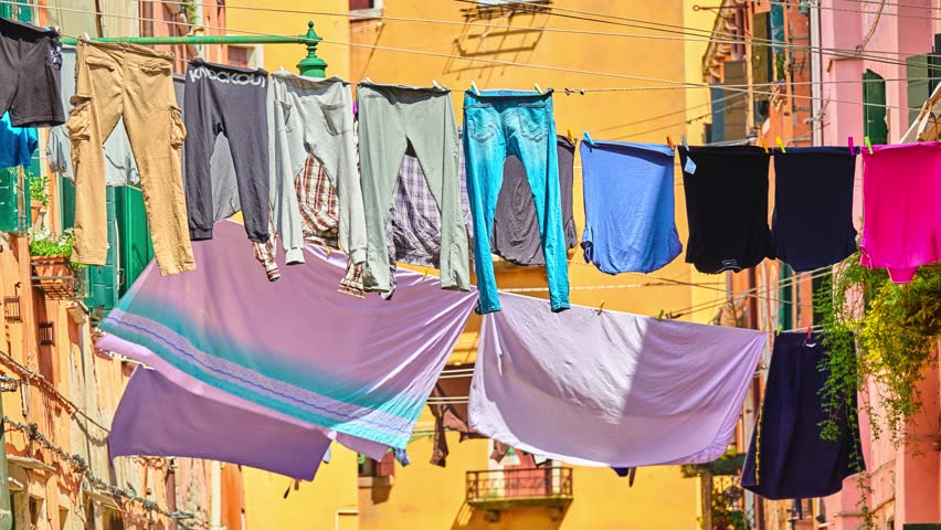 Washed clothes are dried on ropes with clothespins on background of yellow houses in small European city | Shutterstock HD Video #1011494210