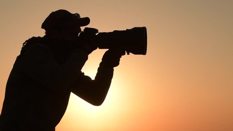 Safari Outdoor Photographer at Sunset. Silhouette of Men Keeping Digital Camera in Hand with Large Telephoto Lens For the Better Wildlife Closeups. Slow Motion Footage