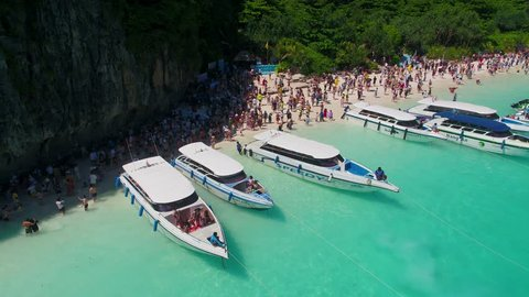 Maya Bay, Koh Phi Phi Leh, Thailand - May 16, 2018. Long tail boats mooring in the famous Maya Bay with tourists on the beach