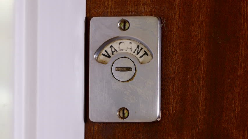 Closeup of someone entering a public toilet / bathroom and closing the wooden door. The sign changes from vacant to engaged.