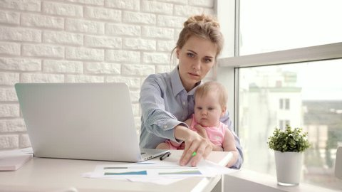 Working mother with baby at table. Busy woman working on laptop with baby on hands. Working mom with beautiful infant on hands in cozy home. Female freelance work. Modern motherhood