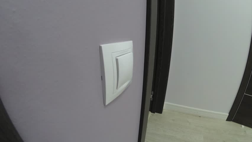 Energy saving - hand turning off a light switch in a house | Shutterstock HD Video #1011532520