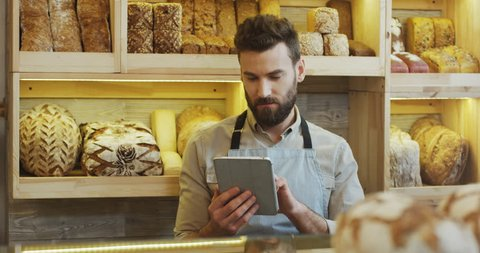 Caucasian young man bread seller scrolling and taping on the tablet computer while standing at the counter in the bakery shop, then looking to the camera. Indoor