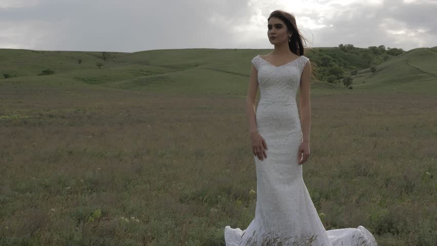 beautiful bride in long white wedding dress stands against large field with grass and cloudy sky
