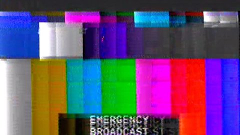 Analog capture (intentional heavy distortion fx): tv transmission, noisy signal of SMPTE color bars (a television screen test pattern) with the text Emergency broadcast.