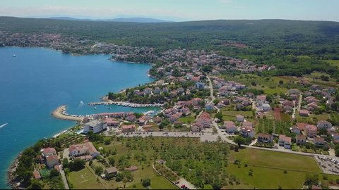 Panoramic view of small village Porat at Krk Island in Croatia. Sunny morning haze covers seaside.