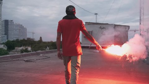 Young man in balaclava with red burning signal flare on the roof with graffiti background, slow motion