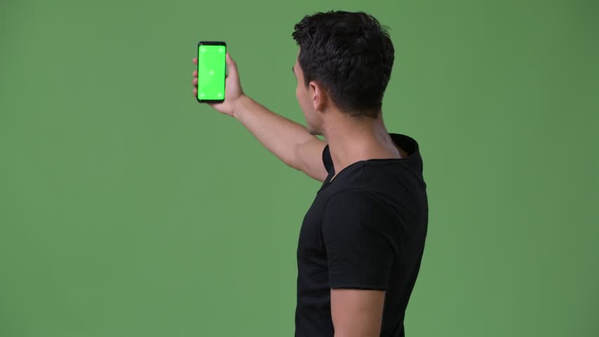 Young handsome Hispanic man w phone against green background | Shutterstock HD Video #1011596120
