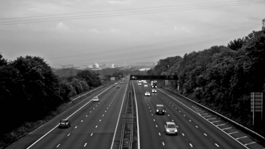 Out of focus slow traffic on M5 Motorway D, Captured in Clapton-in-Gordano, England - black and white high contrast