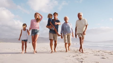 Multi Generation Family On Summer Vacation Walking Along Beach