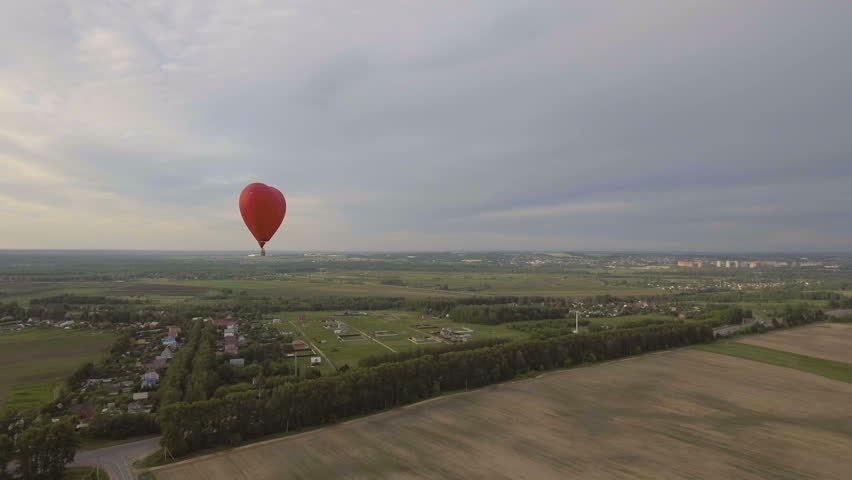 Red balloon in the shape of a heart.Aerial view:Hot air balloon in the sky over a field in the countryside,the beautiful sky and sunset.