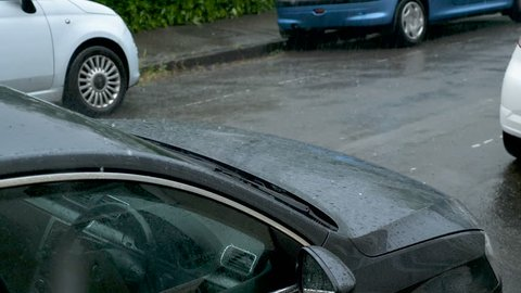Large rain drops and hailstones strike parked cars during heavy shower in England