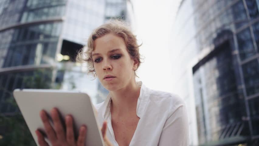 Businesswoman Using a Tablet Computer. Office Buildings | Shutterstock HD Video #1011678440