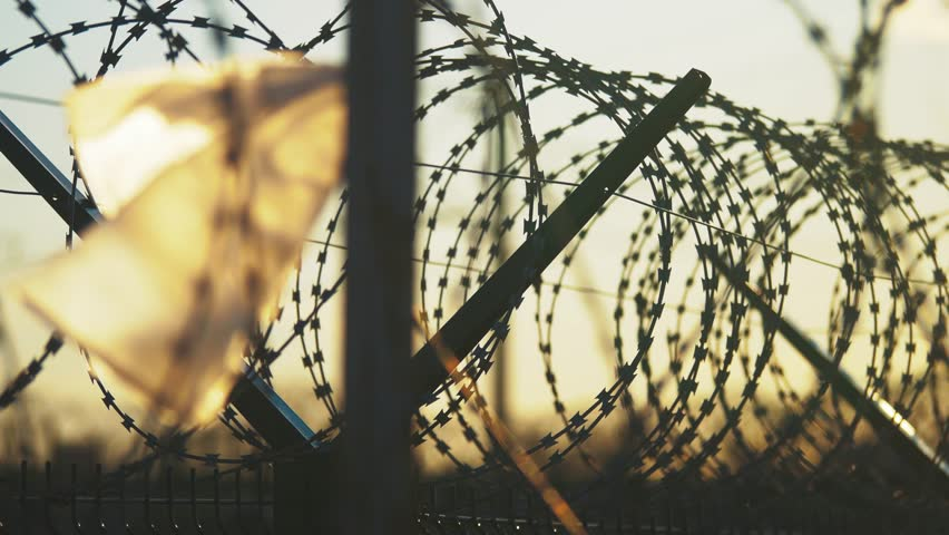 Fence prison strict regime silhouette barbed wire. illegal immigration fence from refugees. illegal immigration concept prison prison fence lifestyle | Shutterstock HD Video #1011682490