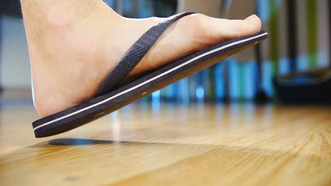 Flat feet in flip-flops step in frame slow motion 4K. Low angle view of person's foot wearing flip-flops in focus while walking into frame stopping. Home dining room in the background out of focus.