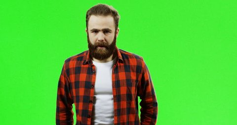 Portrait shot of the very shy Caucasian man with a beard standing in front of the camera on the green screen background. Chroma key.
