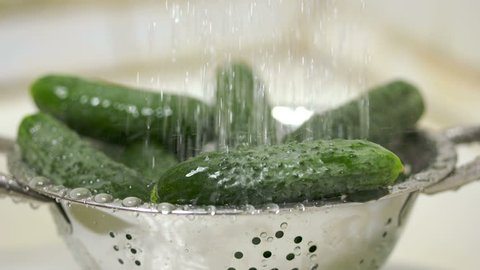 Washing fresh cucumbers in steel colander under running water in slow motion. Rinsing vegetables before cooking and eating.