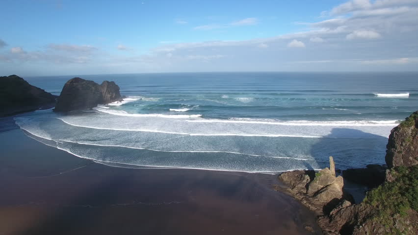 Aerial view of Lion Rock and large surf waves at Piha Beach, Auckland