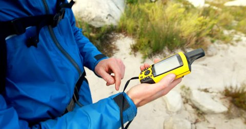 Male hiker using digital anemometer to check the weather in countryside 4k